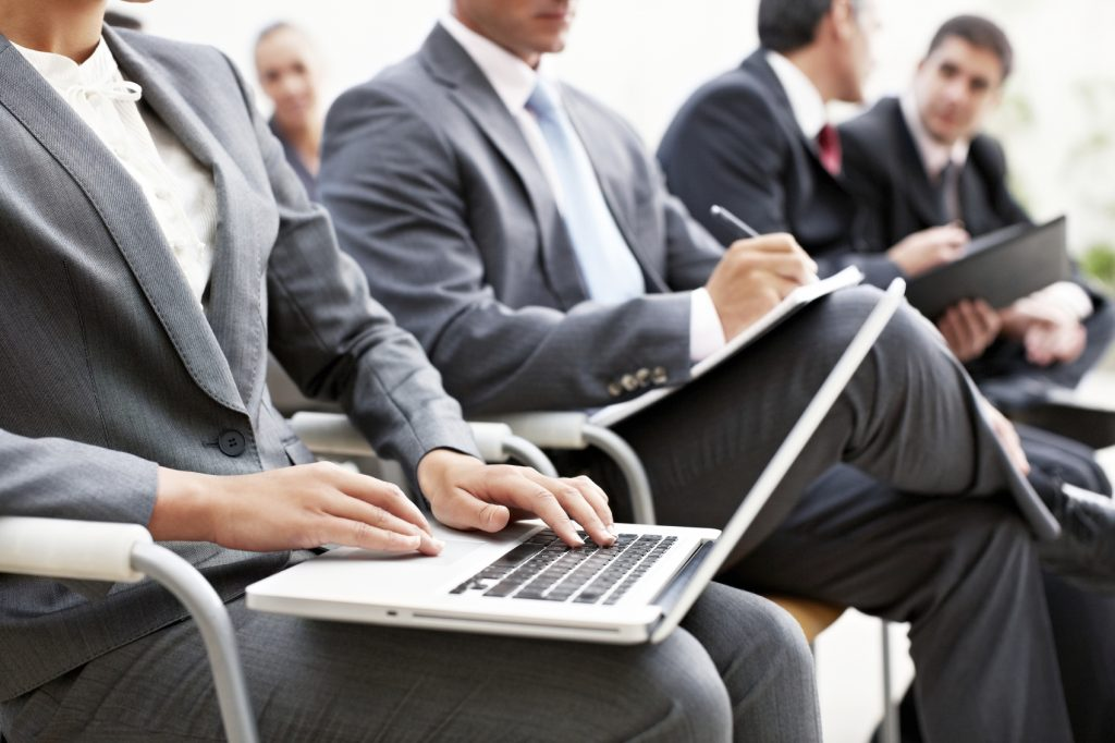 Real Estate Salespeople Meeting with Notes and Laptop