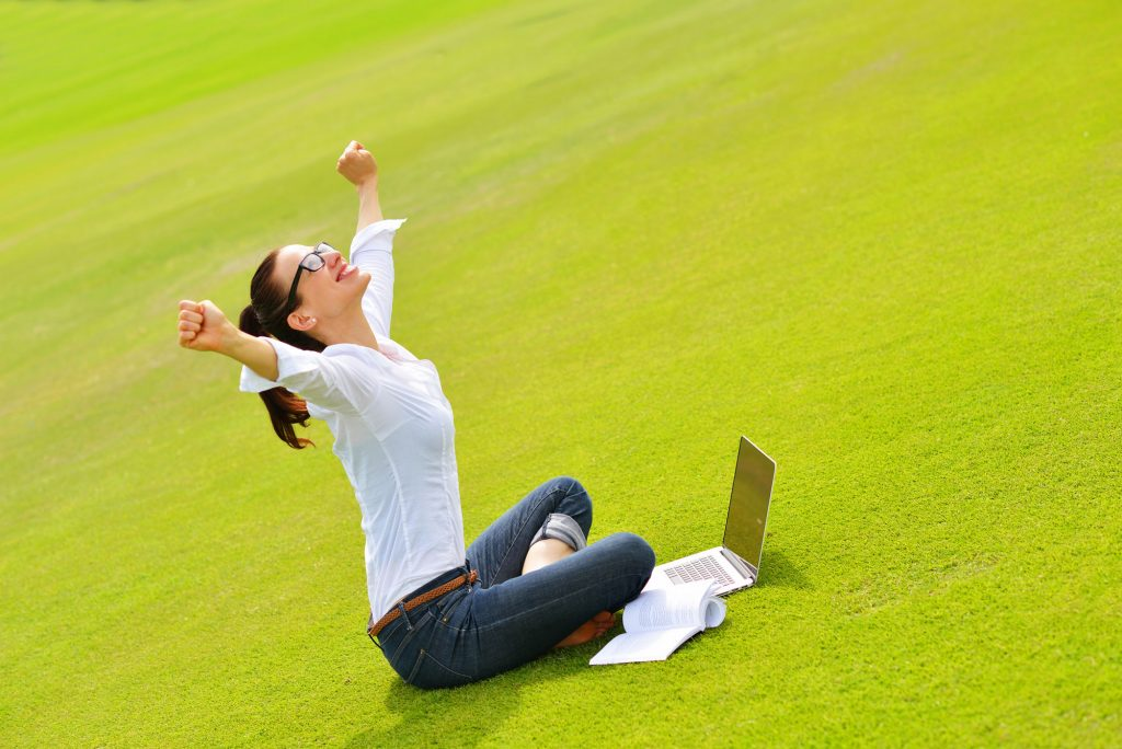 Excited Passit Woman in Park with Laptop
